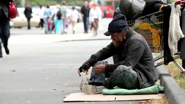 Beggar sitting in the street waiting for coins